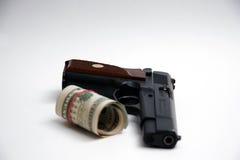 货币手枪和卷  免版税库存图片
