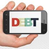货币概念:拿着智能手机以在显示的债务的手 库存图片