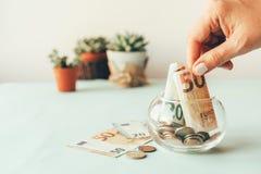 货币积累在一个玻璃瓶子的 免版税库存图片