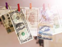 货币 晒衣绳洗涤的货币 色的晒衣夹 免版税库存图片