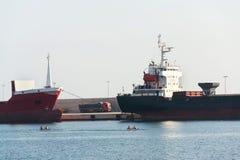 货物卡车站立在缓慢货船在运输港口,荡桨在前景海,口岸Monopoli,意大利的划桨手之间 免版税库存照片