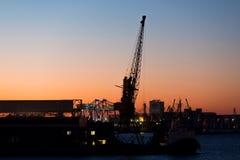 货物在日落天空背景的口岸起重机  库存图片