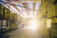 货物纸板箱在后勤存储仓,里面仓库内部里与阳光 库存照片