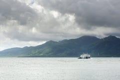 货物轮渡在季风风暴重的云彩下的热带海和天际的热带酸值张海岛在泰国 库存照片