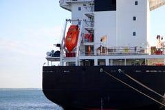货船关闭 有橙色救生艇的货物船 免版税库存照片