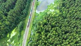 货车运载与煤炭一个电力机车由两面的铁路在Ural沼泽的湖在空中的森林- 影视素材