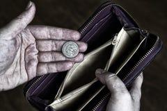 贫困者的肮脏的手举行一美元的四分之一和 图库摄影