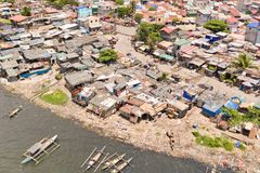 贫民窟在马尼拉,一张顶视图 恶劣的人和小船议院在恶劣的区域 由家庭废物的海污染 免版税库存照片
