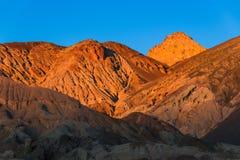 贫瘠沙漠山和高山焕发在金黄小时在一完善的天空蔚蓝下的日落内 图库摄影