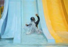 贬低幸福的亚裔儿童男孩滑子对游泳池,孩子学习活动概念 库存图片