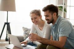 购买网上举行的信用卡的愉快的夫妇 库存图片