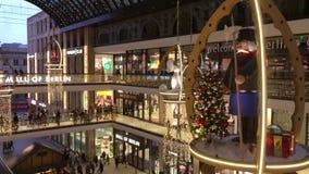 购物'柏林购物中心'装饰为圣诞节,繁忙与许多顾客和照亮与数千光 股票录像