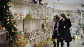购物中心的两名妇女在平安夜,走通过架子有很多圣诞装饰和选择圣诞节 股票视频