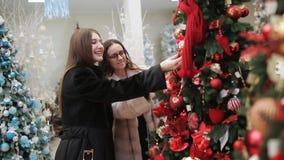 购物中心的两名妇女考虑新年装饰的垂悬在站立在销售区域的人为树 股票录像