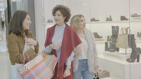 购物中心的女孩穿昂贵的衣服和得到激发和有反应对销售他们在窗口商店看- 影视素材