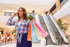 购物中心的女孩谈话在电话 免版税库存图片