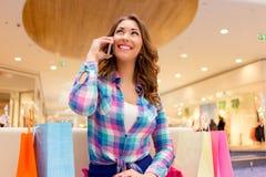 购物中心的女孩谈话在电话 免版税库存照片