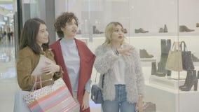 购物中心的富有的女性经理坐在窗口商店前面和谈论一双鞋在销售中- 股票视频