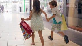 购物假日、弟弟和姐妹有全部的包裹在手上获得乐趣,当购买在购物中心时 影视素材
