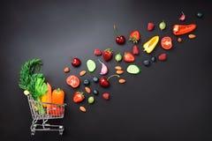 购物台车用新鲜的有机蔬菜、水果和莓果填装了在黑黑板 顶视图 素食主义者 免版税库存图片
