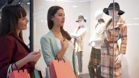 购物周末,近时尚女孩购物窗口在正是季节昂贵的商店谈论新的收藏时髦的衣裳  影视素材