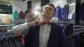购物和时尚概念-年轻人选择和尝试的夹克在购物中心或服装店 股票视频