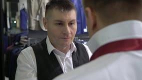 购物和时尚概念-年轻人选择和尝试的夹克在购物中心或服装店 影视素材