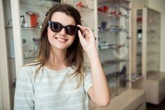 购物和生活方式概念 站立在有愉快的表示的眼镜师商店的可爱的欧洲女性顾客 图库摄影