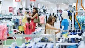 购物在商店 儿童` s衣物部门 女孩,孩子,在商店选择事 小时尚女孩 股票录像