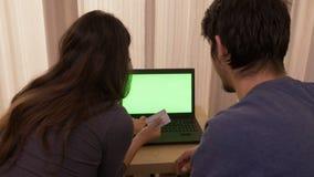购物在网上从家的富感情的年轻夫妇使用有绿色屏幕的一台膝上型计算机 影视素材