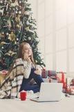 购物在网上在舒适圣诞节内部的少妇 免版税库存图片