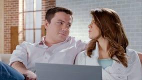 购物在膝上型计算机的年轻夫妇,一起选择假期游览,预定 库存照片