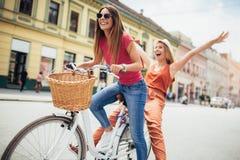 购物在自行车的两名美丽的妇女在城市 免版税库存图片