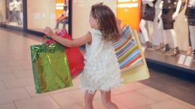 购物天,有包裹的愉快的儿童女孩到手里通过购物中心追捕在时尚精品店的购买 影视素材
