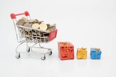 购物概念、台车、硬币和礼物盒 免版税库存图片