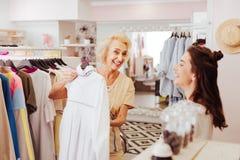 购物的上瘾的母亲和女儿获得乐趣在陈列室 免版税库存图片