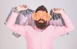 购物的上瘾的消费者 如何准备好在您的下个假期 人有胡子的行家穿戴太阳镜一会儿运载全部 库存照片