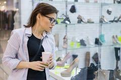 购物的成熟妇女,女性看与鞋子的一个商店窗口,购物在购物中心 库存照片