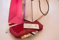 购物的概念,购物纸袋、卡片、钱包和标记与文本染黑星期五 免版税库存照片