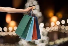 购物袋和信用卡在手中在圣诞节 库存图片