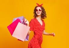 购物购买的愉快的少女概念和销售有包裹的在黄色背景 图库摄影
