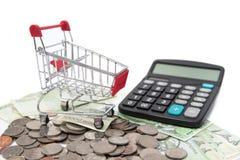 购物车和计算器在被堆积的硬币和钞票 免版税库存照片