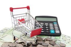 购物车和计算器在被堆积的硬币和钞票 库存照片