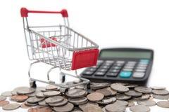 购物车和计算器在被堆积的硬币和钞票 免版税图库摄影