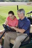 购物车夫妇打高尔夫球微笑 免版税库存照片