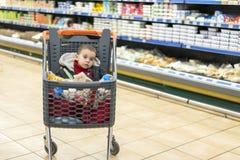 购物车的-台车美丽的婴孩 有孩子坐的产品的一辆台车 充分的推车用食物在超级市场 免版税库存照片
