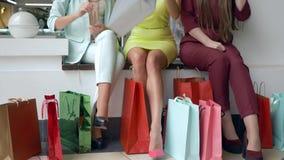购物销售,公司时髦的女人观看新的购买正是季节折扣和许多生动的包裹在腿附近 股票视频