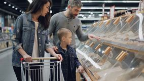 购物食物在超级市场指向在架子和谈话的塑料盒的母亲、父亲和他们的儿子 股票录像