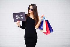购物 妇女在ligth背景的holdingdiscount空白在黑星期五假日 库存图片