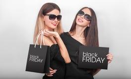 购物 拿着在轻的背景的两名妇女黑袋子在b 免版税库存照片
